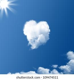 Cloud-shaped heart on a blue sky and sun