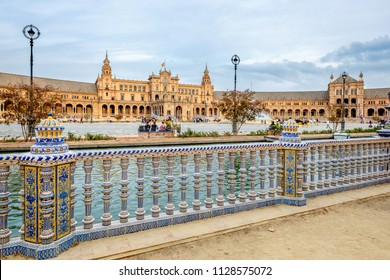 A cloudy autum day, filled with tourists walking the sqaure  in Plaza de Espana in Sevilla Spain