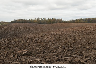 Cloudy autumn day with plowed field in countryside