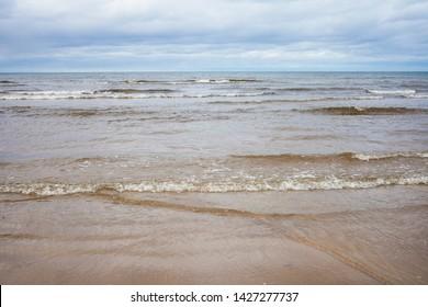 Cloudy autumn day at seaside. Baltic sea wind and waves. Latvia, Jurmala beach.
