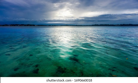 Cloudy blue background sunset from the island of Panamanian archipelago with clear turquoise water of the Caribbean sea and bright sunrays breaking true the grey clouds showing tropical scenery.