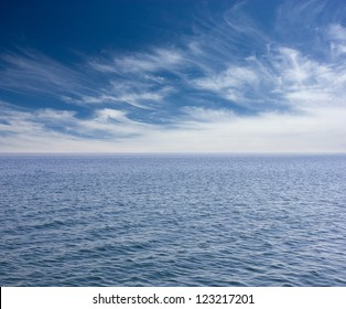 Cloudy blue sky above a blue surface of the sea