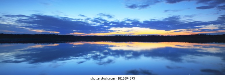 Cloudy blue sky with glowing golden sunset clouds above the forest lake. Symmetry reflections on the water, natural mirror, texture, background. Idyllic rural scene. Latvia. Picturesque panoramic view