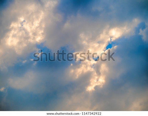 Cloudy blue sky with interesting light patterns.