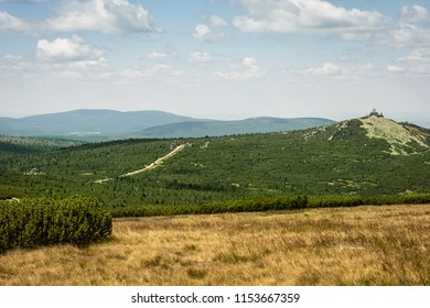Cloudy blue sky, rocky green hill and yellow grass in the Giant Mountains in Poland, Central Europe