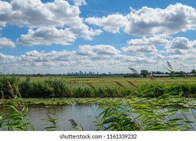 Cloudy blue sky and skyline of Rotterdam city seen from a polder canal, close to Rotterdam, Netherlands.