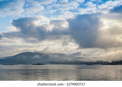 Cloudy dawn in Arousa bay with fog over Vilagarcia at background