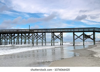 Cloudy evening at atlantic ocean beach. Atlantic ocean waves, scenic view with the wooden pier at Pawleys Island, South Carolina, Myrtle Beach area, USA.