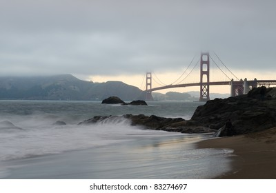 Cloudy and foggy Golden Gate Bridge with Baker Beach in San Francisco