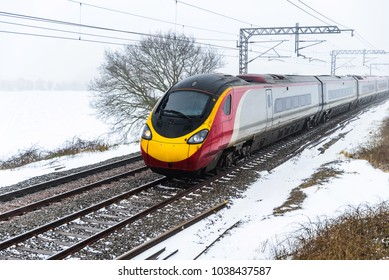 Cloudy foggy winter day view of Train on UK Railroad in England. Emma storm railway landscape.