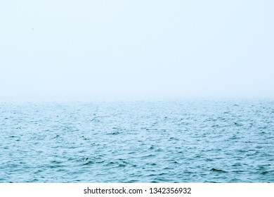 Cloudy horizon and fog over the sea waves, natural background. Fog sea background. Abstract image of sea with fog.