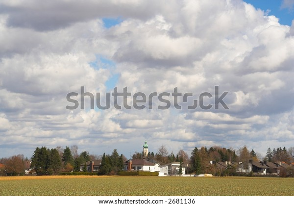 Cloudy landscape with houses and church