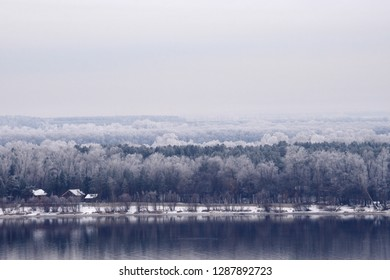 Cloudy landscape of Volga river in winter / Leafless forests and green pine trees on the bank of Volga river