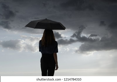 cloudy and menacing sky with silhouette of person with umbrella