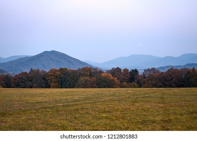 Cloudy morning on the meadow, forest with autumn leaves and Beskydy mountains in the distance