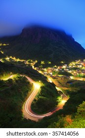 Cloudy mountain and light trail on a curve at evening