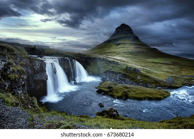 Cloudy overcast day of the Kirkjufellsfoss Waterfall with Kirkjufell mountain in the background in Iceland.