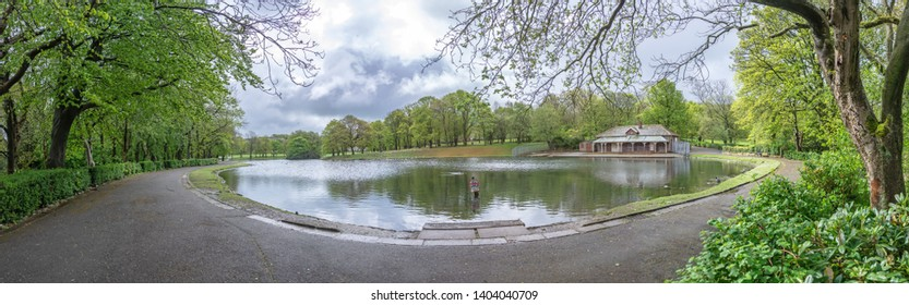 Cloudy overcast panoramic photograph of boating lake at Queens park Blackburn Lancashire