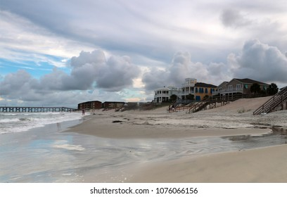 Cloudy seascape at Pawleys Island with dramatic evening sky over atlantic ocean beach with a pier and waterfront houses for vacation rentals. Myrtle Beach area, South Carolina, USA.