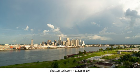 Cloudy skies start to clear after a storm making a rainbow behind the buildings of New Orleans Louisiana