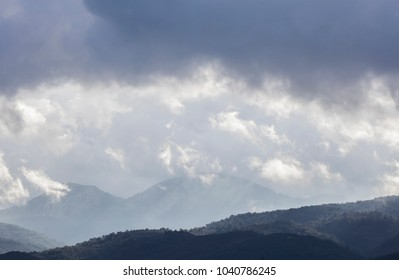 cloudy sky above the green  hills and trees