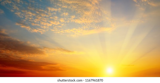 Cloudy sky and bright sunrise over the horizon. Wide photo .