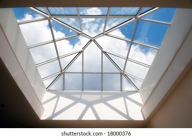 Cloudy sky captured by the  glass roof of modern building