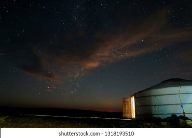 Cloudy sky full of stars in Mongolia. Milky way in view at night in the summer sky of Mongolia. Cloudy skies filled with stars with orange tinge from the moon not in view.