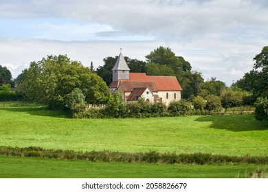 The cloudy sky over the field and old chapel with a weathervane on top of its tower