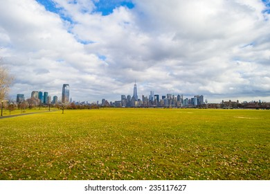 Cloudy Sky Over Jersey City and New York City in Autumn Season. Looking faraway, the left side is Jersey City and the right side is New York City. The front ground is Liberty State Park, New Jersey.