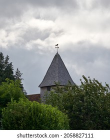 The cloudy sky over the old building with a weathervane on top of its tower