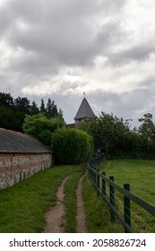 The cloudy sky over the road leading to old building with a weathervane on top of its tower