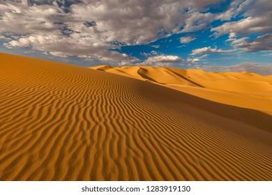 Cloudy sky over sand dunes in the desert.