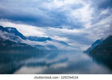 Cloudy sky over the Sorfjord (Sorfjorden) fjord, branch of greater Hardangerfjord (Hardangerfjorden), Folgefonna glacier seen on Hardangervidda mountain plateau. Hordaland county, Norway, Scandinavia