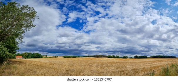 """Cloudy sky over a wide hilly landscape at the cycling route """"Tour Brandenburg"""" in the """"Maerkische Schweiz"""" area near the town of Moeglin - panorama from 7 pictures"""