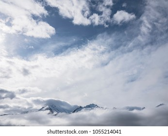 Cloudy sky with snow covered mountain peaks emerging from fog.