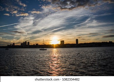 Cloudy sky with sunset over city and Hudson River