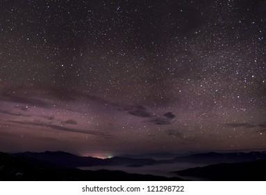 Cloudy star night, fog, mountains and city lights far away. Night panorama of highest Ukrainian peaks.