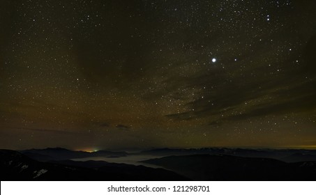 Cloudy starry sky over foggy mountain ridges