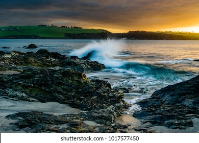 A cloudy sunrise drifts over the Rocks at Spit Beach in St Austell, Cornwall as the waves crash against the highly textured rocks. The view is from Spit Beach across St Austell Bay and into Polkerris.