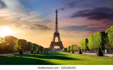 Cloudy sunrise and Eiffel Tower on Chaps de Mars in Paris, France