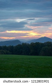 Cloudy sunrise on the green meadow, dark forest and Beskydy mountains in the distance