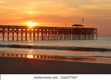 Cloudy sunrise over Atlantic ocean. Beautiful marine landscape with sun rising over calm atlantic ocean beach with wooden pier. South Carolina, Myrtle Beach area, USA. Vacation background.