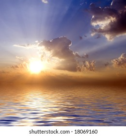 cloudy sunrise with sunbeams blue sky with reflection in water surface