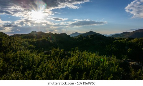 Cloudy sunset with blue sky and green nature visible in a scene on the plains of the Mantiqueira mountain in Brazil.