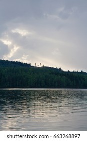 Cloudy sunset. Lake, forest, mountain range and two separate trees.