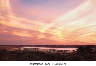 cloudy sunset over the Guadiana river between Portugal and Spain as seen from Costa Esuri, Ayamonte
