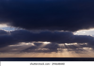 cloudy sunset over ocean, sunbeams are coming through the gaps