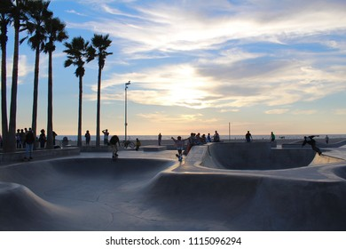 Cloudy Sunset over Venice Beach Skate Park leaving shadows over the ramps with surrounding palm tree silhouettes and skaters