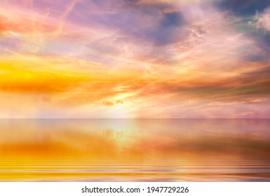 cloudy sunset at sea yellow pink blue pastel colors  sun  beam reflection on light blue sea water nature lanscape